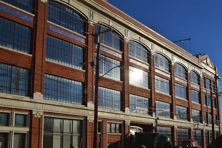 exterior of a red brick building with large framed windows with the sun reflecting off of the windows. a green cement truck sits at the base of the building.