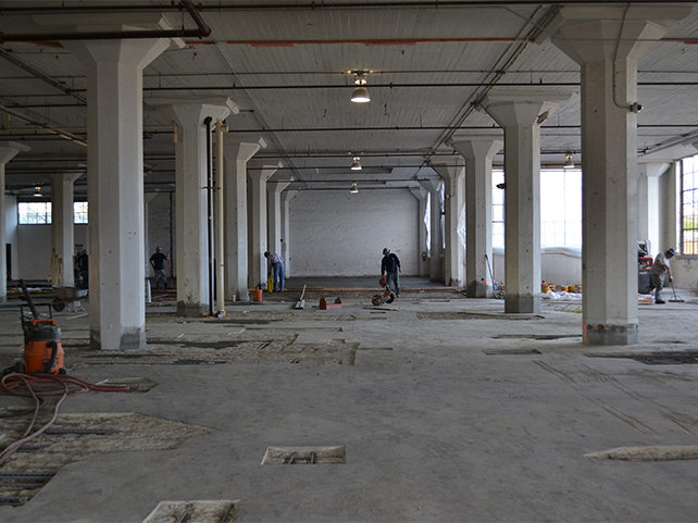 workers inside of an open, white building with large white pillars in in the middle the building