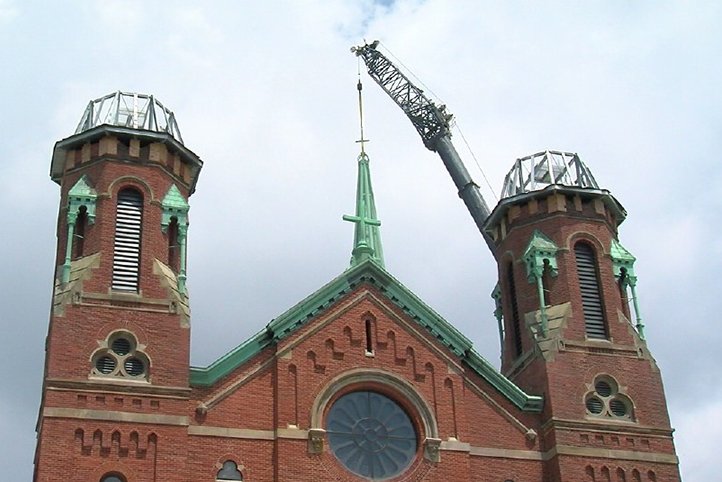 A crane lifts a copper patina steeple onto an historic church as part of the Crossroads Uptown construction project.