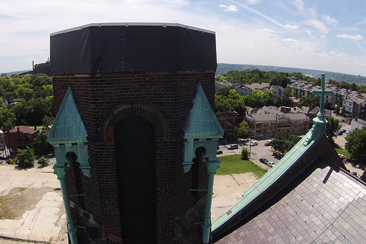 An image of the burnt and damaged bell tower, octagonal with red brick and copper patina detailing. It was restored and repaired as part of the Crossroads Uptown construction project.