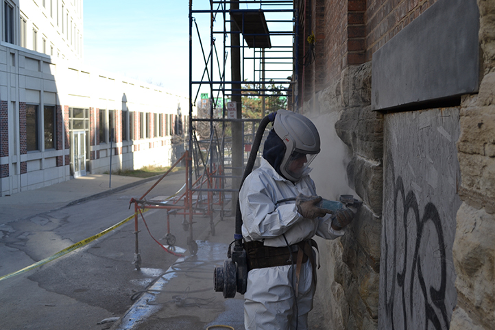 A worker in a full white suit of Personal Protective Equipment stands in front of scaffolding and cleans and restores the stonework at the foundation of the Old Saint George church as part of Crossroads Uptown project.