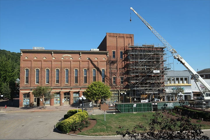 stuart opera house undergoing construction with a crane above the building to take and deliver material. Scaffold covers the front of the building.