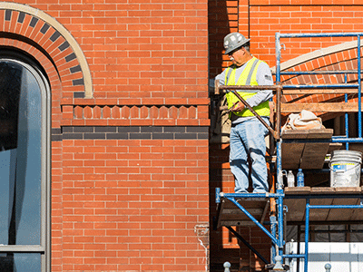 A mason stands on scaffolding and carefully works to restore the red and brown brick work around an arched window as part of restorations to Cincinnati Music Halls iconic facade and hall