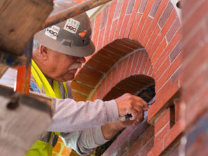 A close up of a mason carefully works to restore the red and brown brick work around an arched window as part of restorations to Cincinnati Music Halls iconic facade and hall