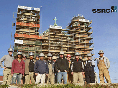 group of SSRG employees standing in front of a building in the background that is covered in scaffolding