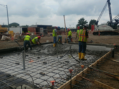 A crew in neon green work shirts work on laying a concrete foundation under a gray cloudy sky with a variety of construction equipment in the distance