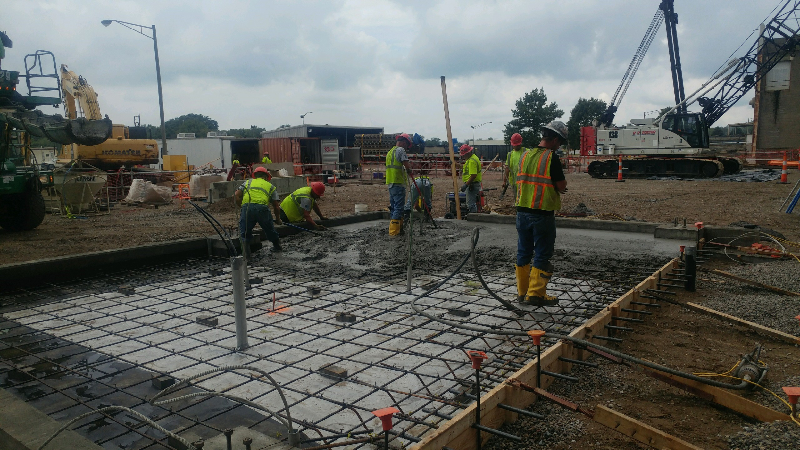 8 workers in high visibility vests spreading freely poured concrete