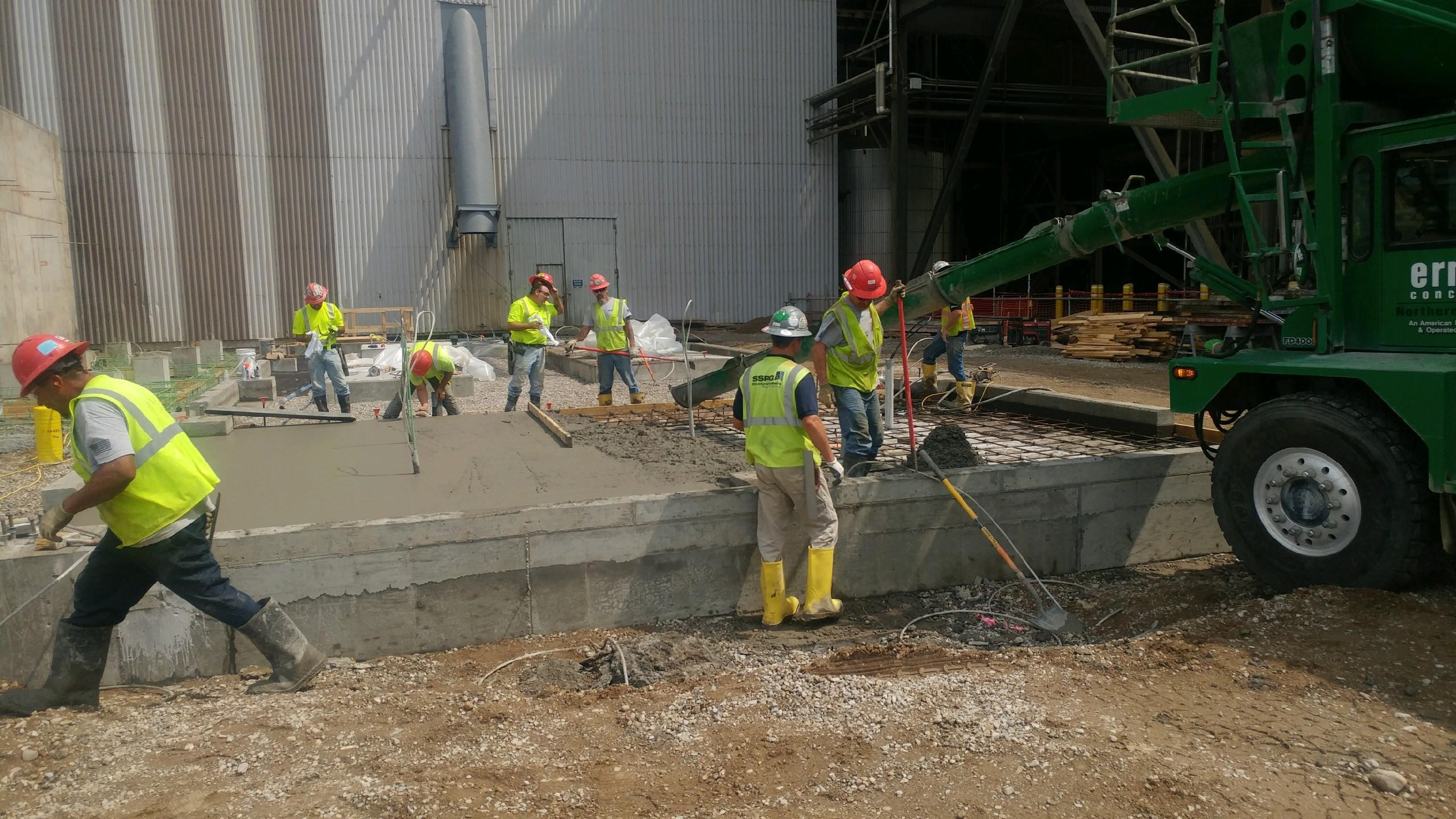 8 workers in high visibility vests spreading freely poured concrete with the green concrete truck on the right side of the photo