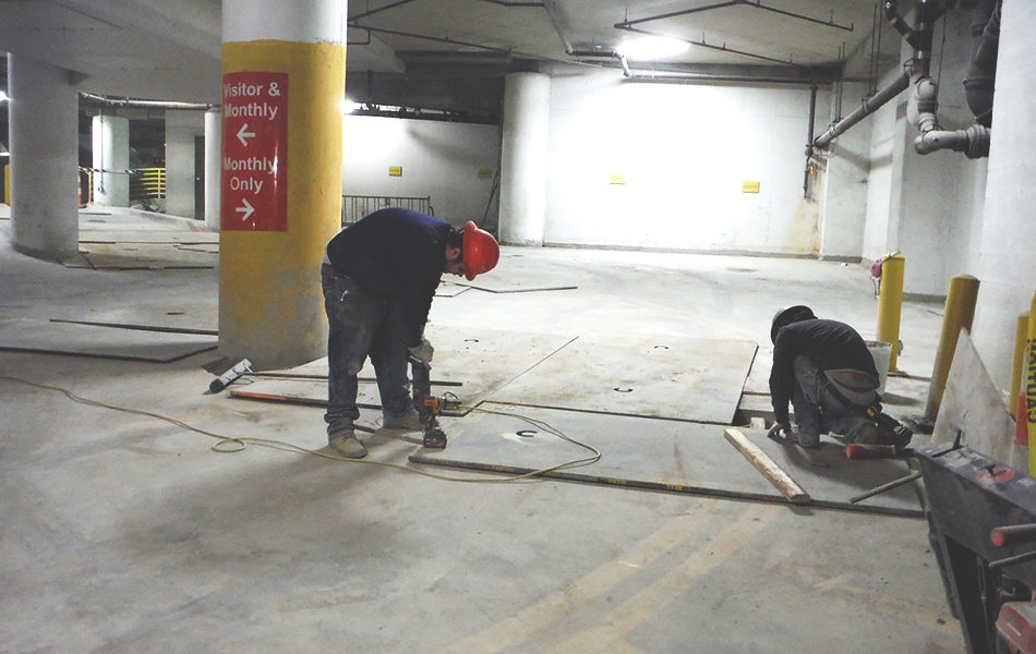 workers in red hard hats working on concrete floor