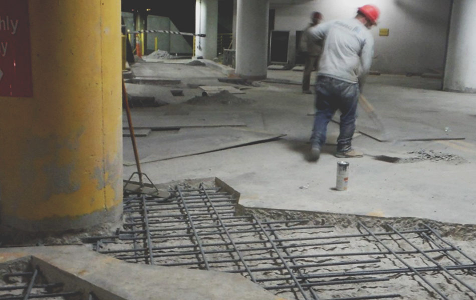workers in red hard hats cleaning up concrete floor