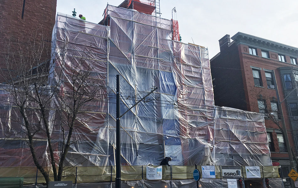 plastic wrap covering the front of the first lutheran church and scaffold