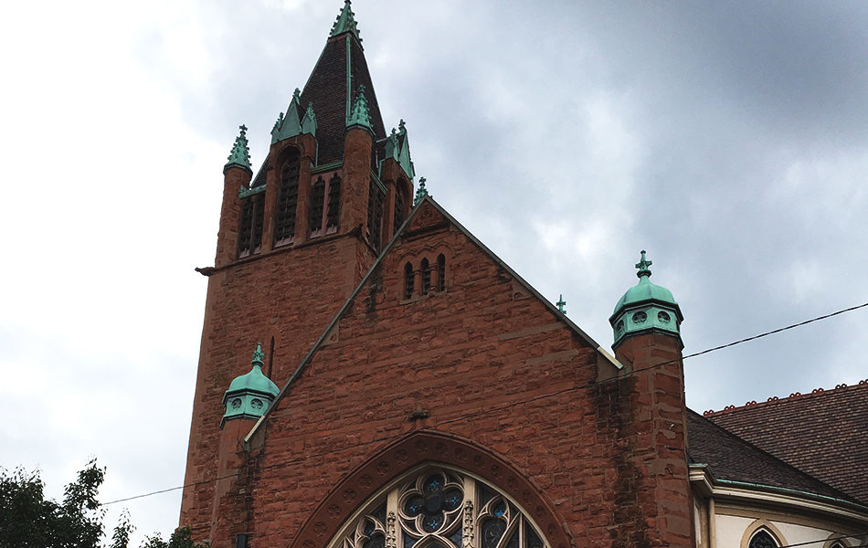 outside shot of the first lutheran church, patina is on the caps of the various roof toppers