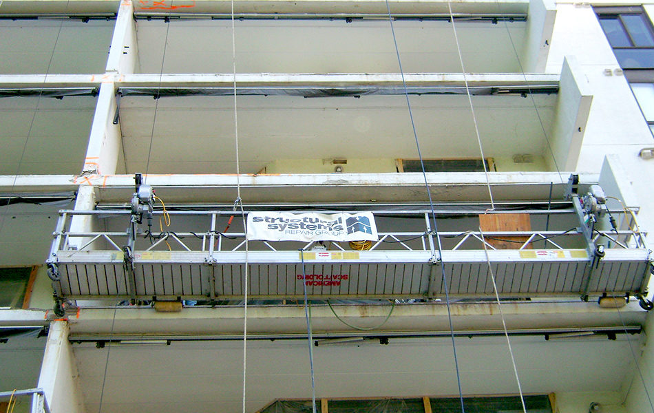 moving scaffold on the outside of a building with a white SSRG banner on the railing.
