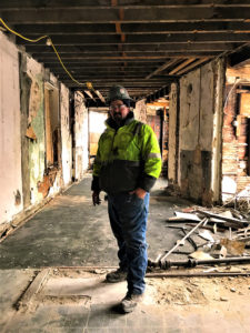 Worker in high visibility jacket standing in the center of the picture in an old building being restored in Mt. Auburn