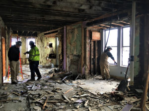 3 workers in an old building performing restoration work