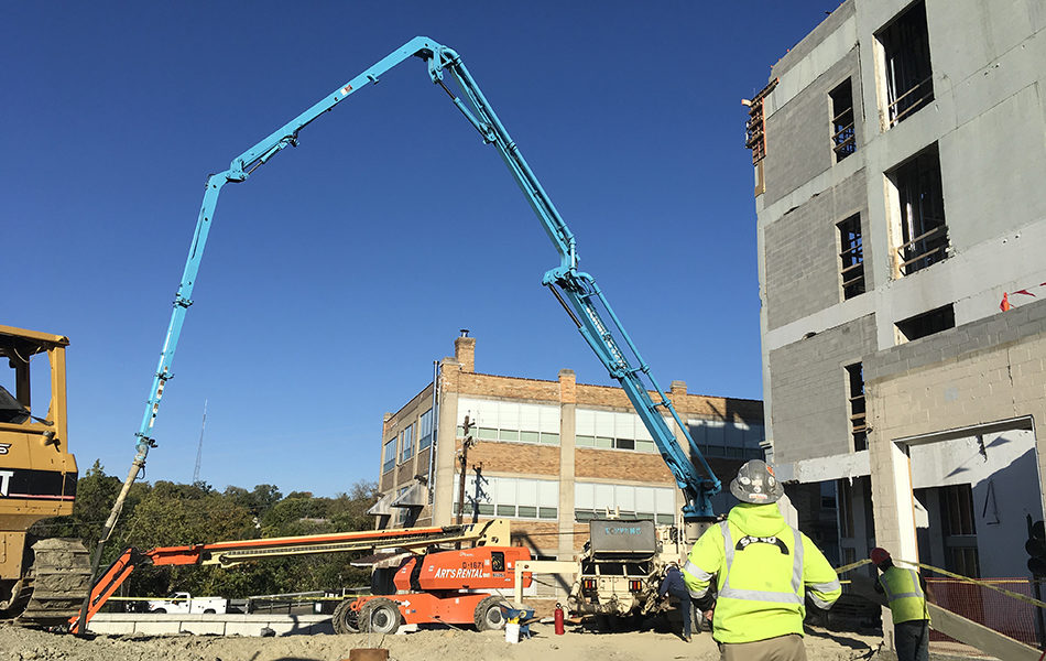 A construction site. Two workers in hi-vis shirts stand facing away from the camera, watching the two cranes. An orange crane is nearly parallel to the ground, while the blue crane pump makes an arc. On the right is the building, mostly concrete framing and cement block with large empty windows.