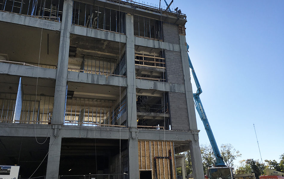 A construction site. A four-story building with mostly only metal and cement framework. A large blue crane extends up to the top story. The sky is bright blue.