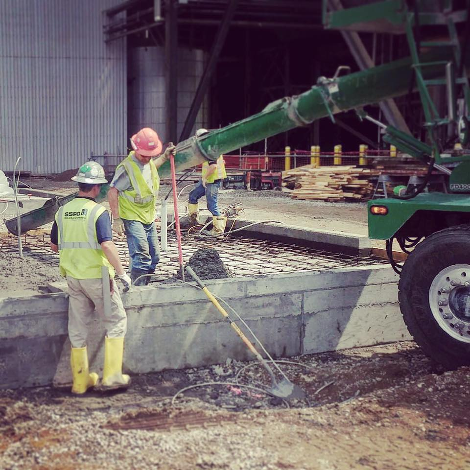 Commercial concrete contractors, overseeing a large-scale concrete pour.