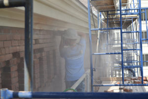 SSRG worker doing cutting brick on the exterior facade of a brick building