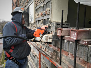 worker in mask using chainsaw to cut cement blocks on exterior of building