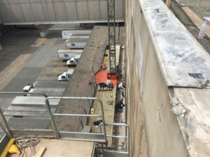 Downward shot of two workers, attached by harness to the we all of a building.