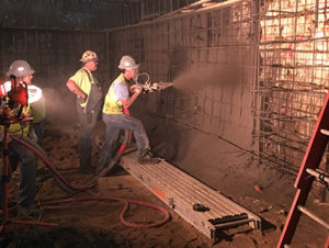 Side shot of 3 workers in high visibility vests, in a dark space, spraying concrete onto the walls of the space.