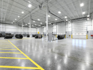 Large, white and grey warehouse with yellow caution lines painted on the floor. Black, heavy duty tires sit in racks around the warehouse.