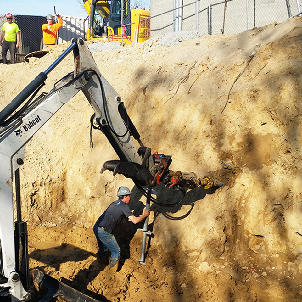 A construction worker in a green hard hat and a navy blue shirt supervises heavy machinery as part of geotechnical stabilization services