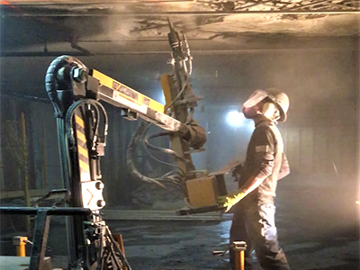 Worker with a high protection helmet with a mask, using a large, yellow chipping hammer on the ceiling of a concrete structure.