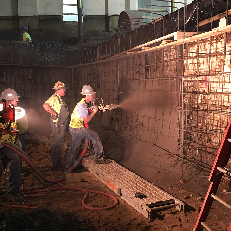 Three construction workers in a dark building spray concrete to build a wall, illuminated by work lights