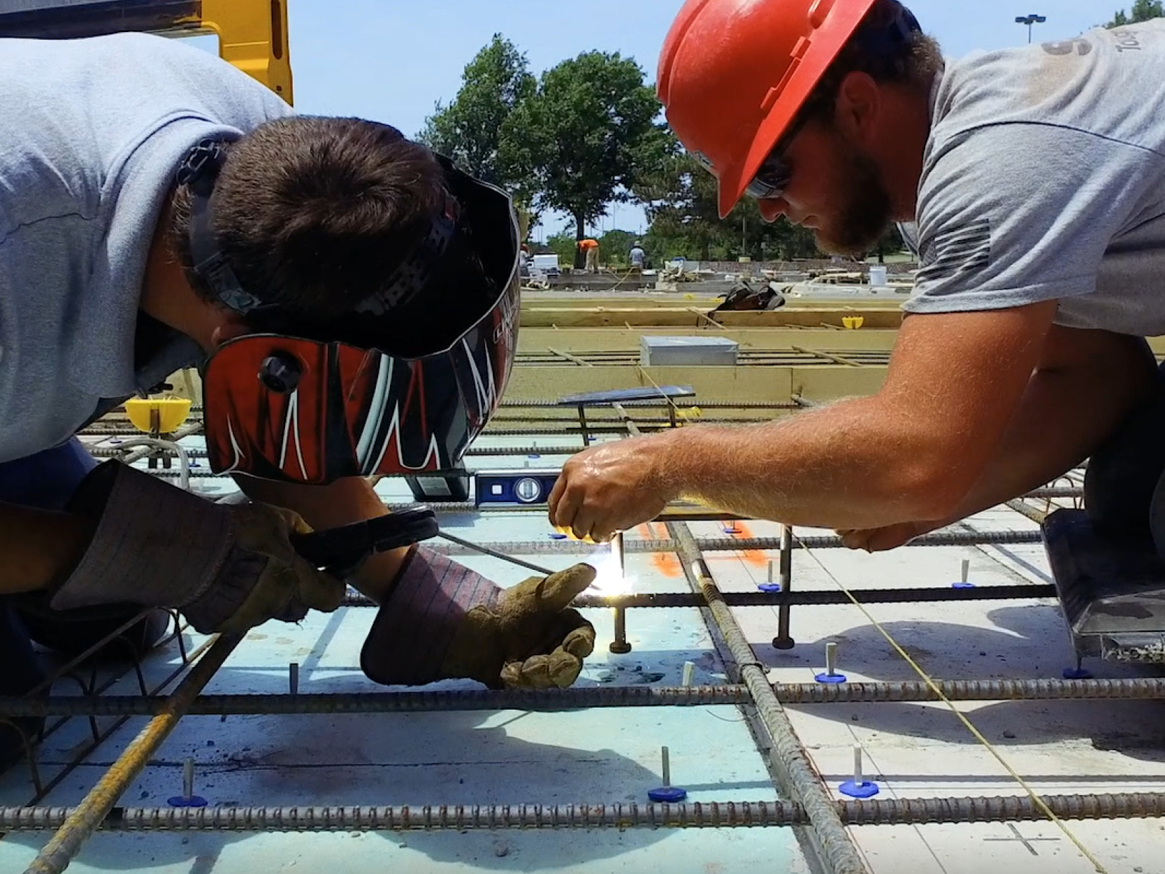 Two construction workers leaning over rebar and concrete as part of the CubeSmart tilt-up project