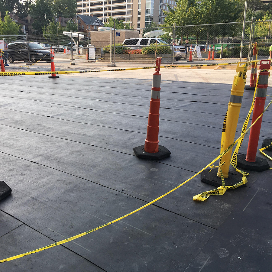 Recently finished waterproofing on a new parking lot. Cones and caution tape mark off the area.