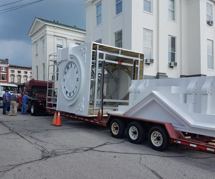 A brand new, large, white clocktower sits atop a long, red, flatbed trailer as it awaits to get unloaded and assembled and installed on the Clark County Courthouse