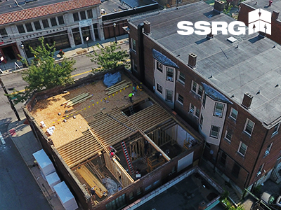 Aerial view of a one-story building with SSRG crew leading construction taking place to prepare for new rooftop bar. One third of the roof is covered, one third shows beams being installed, and one third is open air.