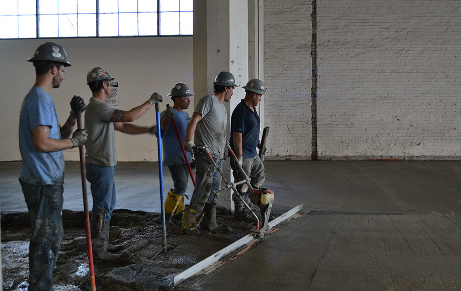 Five men working on a concrete pour. They wear t-shirts, jeans, and high rubber boots in addition to their protective eyewear, gloves and hardhats. They stand in a row, preparing to smooth the most recent pour of concrete. They are in a garage that is under construction.