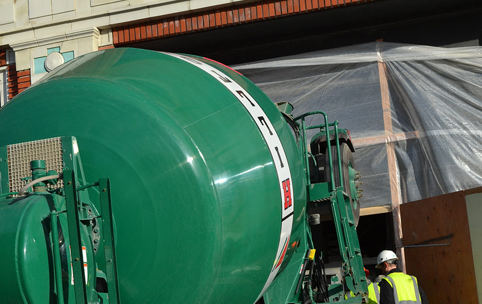 A large green cement mixer is up against a building under construction. Two workers in hi-vis safety vests stand next to the mixer and supervise the concrete pour.