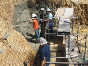 4 construction workers in a hole in the ground. One employee in an orange shirt is spraying the walls of the hole with cement.
