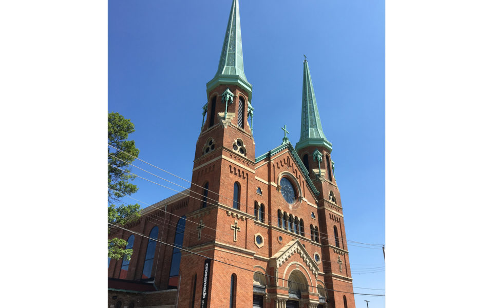 A large church with red brick and tan stones. The stones and bricks work together to create ornate decorative patterns on the facade. Three sets of double doors make up the front entrance. Two tall steeples are on either side of the building. The roofs of the steeples are a light teal color. The sky is bright blue without a cloud in sight.