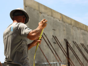 SSRG employee looking away from the camera as he winds up a tape measure. Large cement walls with metal beam braces are in the background.