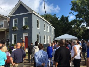 Crowd of people gathered around a for a ribbon cutting for the new youth build house. The grey, two-story house is the centerpiece for the ribbon cutting.