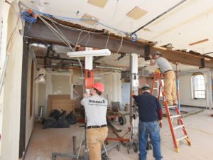 Three SSRG employees in grey and blue shirts working on stabilizing a large, brown, metal beam that runs across the ceiling.