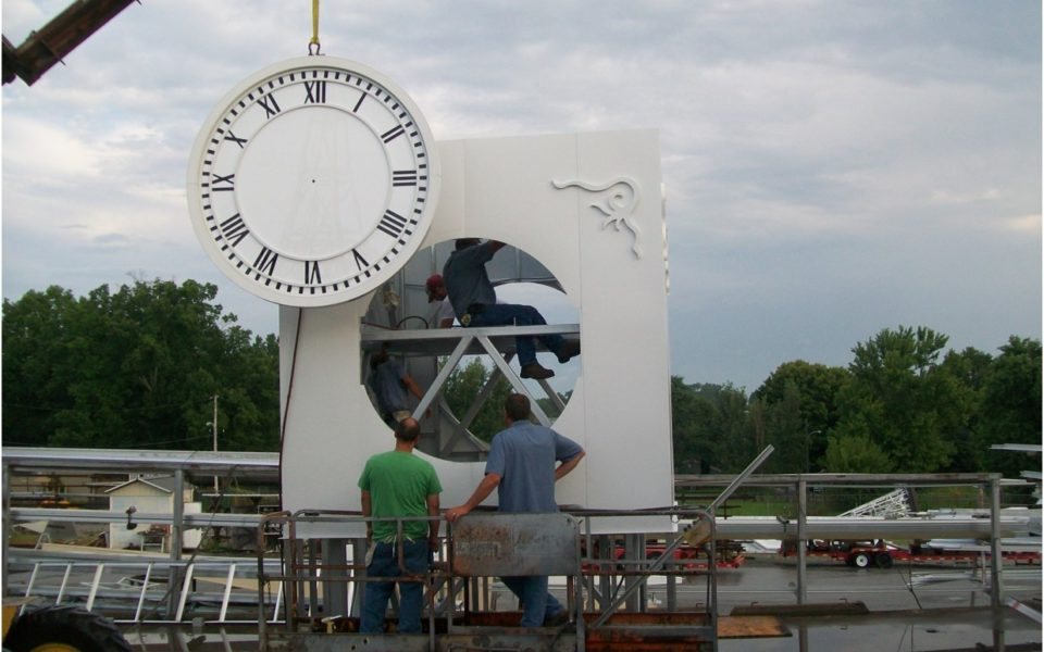 A large clock being assembled by 5 workers for the clark county courthouse