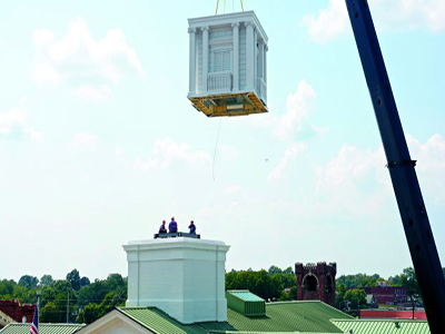 The white clocktower being lowered by crane onto the top of the Clark County Courthouse