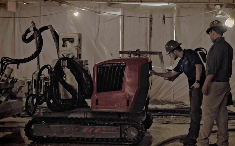 Workers check on the hydrodemolition machine, the AquaCutter