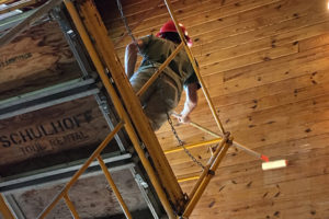 Shot from underneath a scaffold of an employee with a paint roller on a large stick applying a clear coat of sealant to a wooden roof.