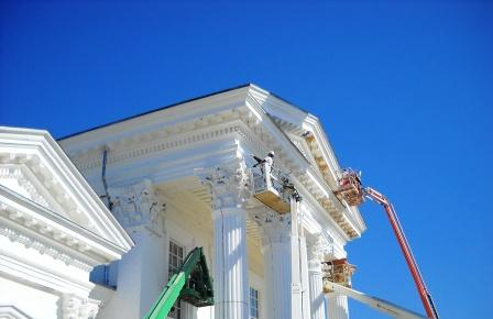 blue sky over white renaissance style building with crane on the front doing work