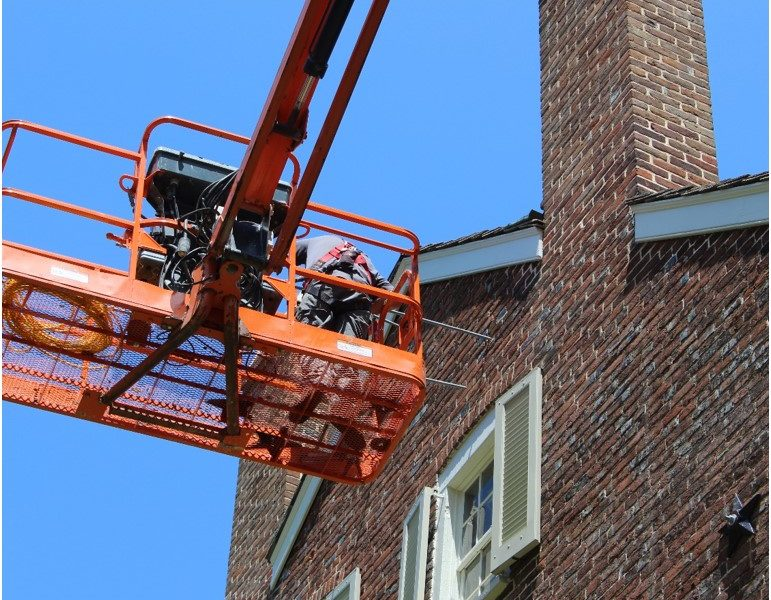 a lift with worker in it repairing the masonry on the side of an historical brick house
