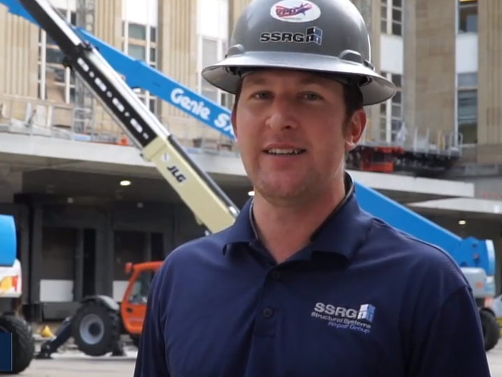 Man in hard hat speaks in front of construction site