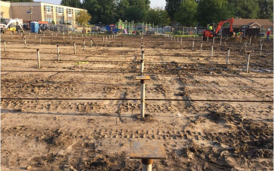 Job site showing helicals embedded in ground in a grid