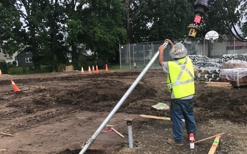 Worker installing helical piles